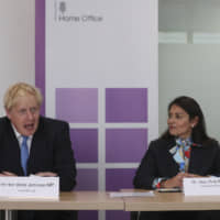 Boris Johnson, U.K. prime minister, speaks as Priti Patel, U.K. home secretary, listens during the National Policing Board meeting in London on Wednesday,. Johnson went a long way toward cementing his working majority in the U.K. Parliament with a visit to Northern Ireland on Wednesday, but did little to break the Brexit impasse with Dublin and Brussels. | BLOOMBERG