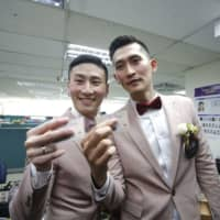 A couple holding identity cards pose for photographs while registering for marriage at a Household Registration Office in Taipei on May 24. | BLOOMBERG