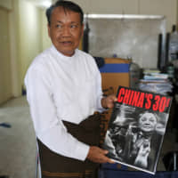 Standing in his office in Yangon on Aug. 1, Aung Shin, editor-in-chief of D. Wave Journal, the magazine distributed by Myanmar's National League for Democracy party, shows off a book he received during a trip to China.   REUTERS