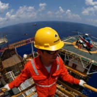 A Rosneft Vietnam employee looks on at the Lan Tay gas platform in the South China Sea off the coast of Vung Tau, Vietnam, last year. | REUTERS