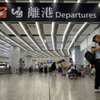 A passenger walks at the departure hall of Hong Kong's West Kowloon Terminus, which connects the city to mainland China by rail, on Tuesday. Britain's Foreign Office said Tuesday it was 'extremely concerned' by reports that a Hong Kong consulate employee had been detained by mainland Chinese authorities on his way back to the city. | AFP-JIJI