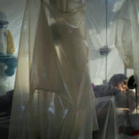 Health workers wearing protective gear check on a patient isolated in a plastic cube at an Ebola treatment center in Beni, Congo, in July. Congo's year-long Ebola outbreak has spread to a new province, with two cases, including one death, confirmed in South Kivu, according to the government health ministry. | AP