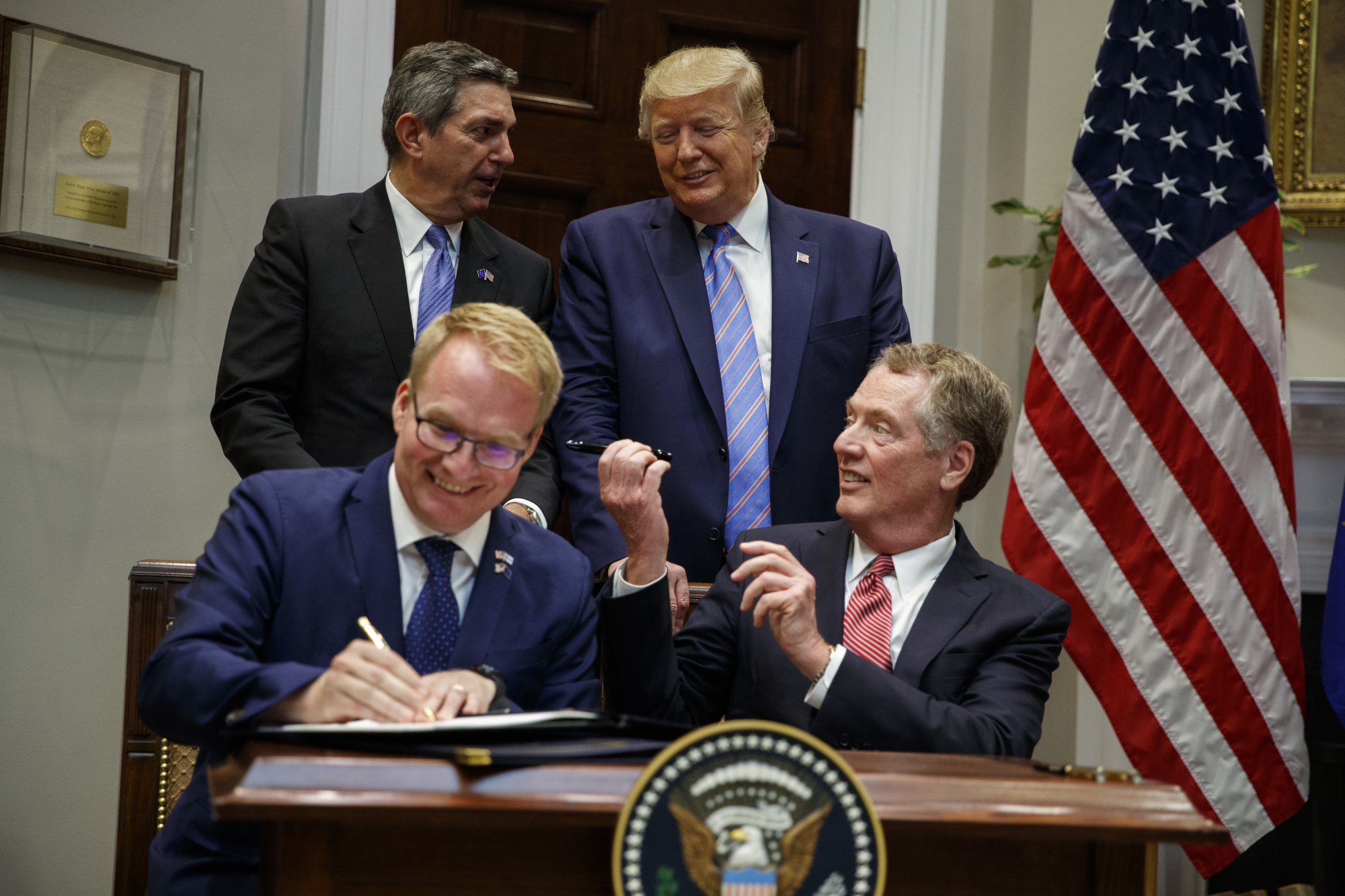 U.S. President Donald Trump talks with European Union Ambassador Stavros Lambrinidis as U.S. Trade Representative Robert Lighthizer (front right) and Jani Raappana, deputy head of mission for the Finnish presidency of the Council of the EU, sign an agreement expanding U.S. beef exports to the European Union, in the Roosevelt Room of the White House on Friday.   AP