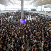 Protesters crowd the departure hall of Hong Kong International Airport on Sunday.   REUTERS