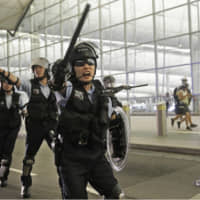 Policemen with batons and shields shout at protesters during a demonstration at the airport in Hong Kong on Tuesday. | AP