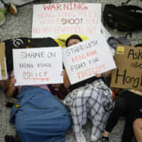 Protesters lie on the floor of Hong Kong's international airport on Wednesday. | AFP-JIJI