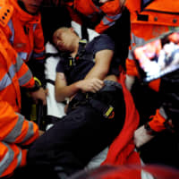 Medics attempt to remove an injured man, who anti-government protesters said was a Chinese policeman, during a mass demonstration at the Hong Kong International Airport on Tuesday. | REUTERS
