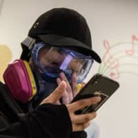 A woman uses her mobile phone in a shopping mall, shortly after frontline protesters told others to leave following the arrival of a police water cannon during a protest in the Tsuen Wan area of Hong Kong on Aug. 25.   AFP-JIJI