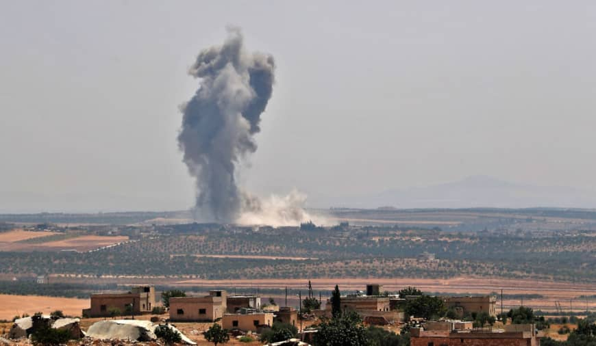 Smoke billows above buildings during a reported airstrike by pro-regime forces on Khan Sheikhun in Syria's Idlib province on Monday. A Turkish military convoy crossed into northwest Syria Monday, heading toward a key town where regime forces are waging fierce battles with jihadists and rebels. | AFP-JIJI