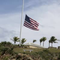 A U.S. flag flies at half-staff on Little St. James Island, in the U. S. Virgin Islands, a property owned by Jeffrey Epstein, Wednesday. Many in nearby St. Thomas are debating what should be done with the structures and even the islands themselves, even though it is unclear who would inherit Little St. James Island and neighboring Great St. James Island. | AP