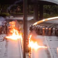 Firebombs thrown toward riot police during a protest in the Admiralty district of Hong Kong on Saturday burn after exploding. Police used water cannons to spray blue-dyed water at defiant protesters, who lobbed the projectiles at them as tensions between demonstrators and authorities escalated on. | BLOOMBERG