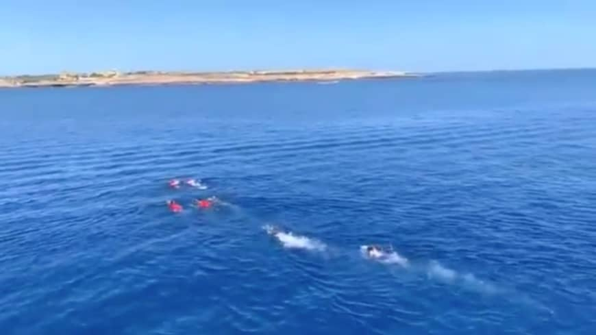 A still image taken from video shows migrants attempting to swim ashore after jumping off the Spanish rescue ship Open Arms off the coast of Lampedusa, Italy, Sunday. | OPEN ARMS / HANDOUT / REUTERS TV / VIA REUTERS