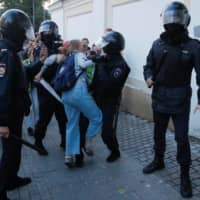 Law enforcement officers detain Muscovite Daria Sosnovskaya after a rally to demand authorities allow opposition candidates to run in the upcoming local election in Moscow Saturday. | REUTERS