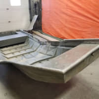 A damaged aluminum boat, recovered from the shores of the Nelson River by Royal Canadian Mounted Police (RCMP) searching for fugitive murder suspects Kam McLeod and Bryer Schmegelsky, is seen in Sundance, Manitoba, Sunday. | MANITOBA RCMP / HANDOUT / VIA REUTERS