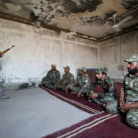 A trainer and member of the paramilitary Popular Mobilization Forces (PMF) explains how to use weapons as part of a military training at the PMF camp in Basra, Iraq, Aug. 4. | REUTERS