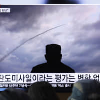 An image of North Korean leader Kim Jong Un watching a missile launch is seen during a news program on a TV screen at Seoul railway station on Thursday. South Korea's military said the North conducted its third weapons tests in just over a week on Friday. | AP