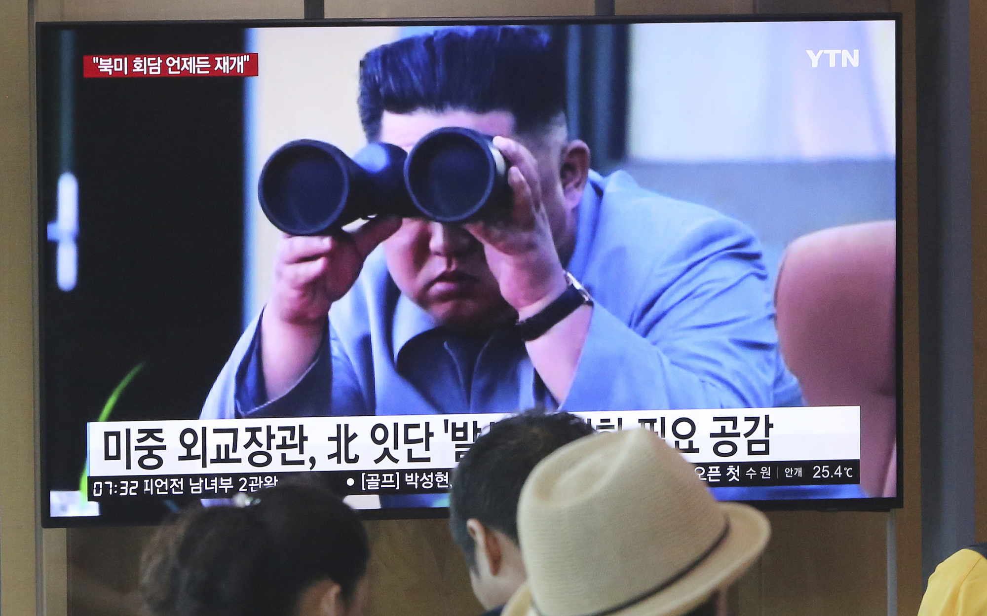 People look at a TV screen at the main railway station in Seoul on Friday during which a news program is broadcasting file footage of North Korean leader Kim Jong Un. | AP