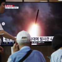 People watch a TV showing an image of a North Korean weapons test, during a news program at the main railway station in Seoul on Thursday. North Korea launched two 'projectiles' for the fourth time in less than two weeks on Tuesday. | AP