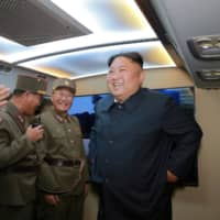 North Korean leader Kim Jong Un smiles as he guides a missile test at an unidentified location in the country in this undated image provided on Wednesday. | KCNA / VIA REUTERS