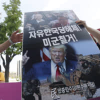 A protester carries a signboard during a rally near the U.S. Embassy in Seoul to oppose joint military exercises between South Korea and the United States on Tuesday. | AP