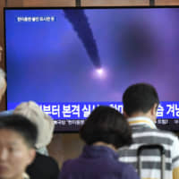 People watch a television showing file footage of a North Korean missile launch, in Seoul on Saturday after the North fired two more short-range ballistic missiles into the Sea of Japan earlier in the day. | AFP-JIJI