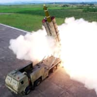 A North Korean missile fires during a test of a 'newly developed super-large multiple rocket launcher' at an undisclosed location Saturday. | REUTERS