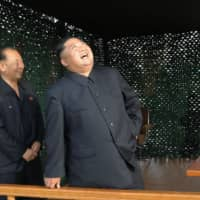 North Korean leader Kim Jong Un beams as a missile is fired during a test of a 'newly developed super-large multiple rocket launcher' at an undisclosed location on Saturday. Kim's sister, Kim Yo Jong (right), also attended the launch. | KCNA / VIA KYODO