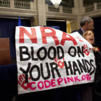 Medea Benjamin, of Code Pink, is led away by security as she protests during a statement by National Rifle Association executive vice president Wayne LaPierre (left) during a news conference in response to the Connecticut school shooting, in Washington in 2012. | AP