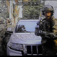 In this image made from a Monday security camera video provided by a neighbor who has requested not to be identified, federal agents conduct a raid on the home of Paige A. Thompson in Seattle. | COURTESY PHOTO / VIA AP