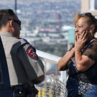 Virginia Chacon reacts as she tells her survival story to a police officer outside the Cielo Vista Mall Wal-Mart where a shooting left 20 people dead in El Paso, Texas, on Sunday. | AFP-JIJI