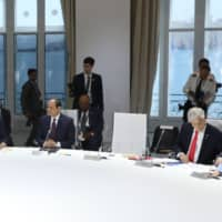 The empty chair of U.S. Presisdent Donald Trump is seen as (from left) French President Emmanuel Macron, Egyptian President Abdel Fattah al-Sissi, Chile President Sebastian Piniera and German Chancellor Angela Merkel attend a work session focused on climate in Biarritz, southwest France, on Monday on the third and last day of the annual G7 Summit attended by the leaders of the world's seven richest democracies, Britain, Canada, France, Germany, Italy, Japan and the United States.   AFP-JIJI