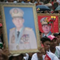 People hold portraits of Myanmar's military chief Min Aung Hlaing during a protest against the U.S., which banned him and three other officers from travel to the country, in Yangon on Saturday.   AFP-JIJI