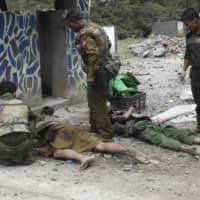 Soldiers stand near two bodies at a police outpost after an attack Thursday in Gote Twin, Naung Cho township, northern Shan State, Myanmar. Members of an ethnic rebel alliance in Myanmar staged coordinated attacks in five locations Thursday in Mandalay Region and in northern Shan State, where 14 people were reported killed. | AP