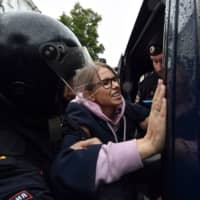 Police officers detain opposition politician Lyubov Sobol as she headed to an unsanctioned rally urging fair elections in downtown Moscow on Saturday. | AFP-JIJI