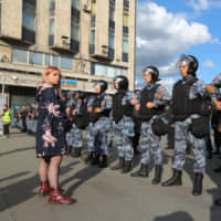 A woman stands near members of the Russian national guard during a rally against the exclusion of opposition candidates from local polls in Moscow Saturday.   BLOOMBERG