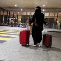 A Saudi woman walks with her luggage as she arrives at King Fahd International Airport in Dammam, Saudi Arabia, Aug. 5.   REUTERS