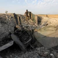 A rebel fighter stands near the remains of a downed regime warplane near the jihadi-held Syrian town of Khan Sheikhun in the south of Idlib province on Wednesday. | AFP-JIJI