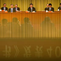 A banner is reflected on a polished surface as Chinese President Xi Jinping (center) speaks during an event to commemorate the 40th anniversary of the 'Message to Compatriots in Taiwan' at the Great Hall of the People in Beijing in January.   REUTERS