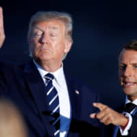 French President Emmanuel Macron and U.S. President Donald Trump (left) prepare for a family photo with invited guests during the G7 summit in Biarritz, France, Sunday. | REUTERS