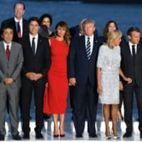 French President Emmanuel Macron and his wife, Brigitte, U.S. President Donald Trump and first lady Melania, Japanese Prime Minister Shinzo Abe, Canadian Prime Minister Justin Trudeau and German Chancellor Angela Merkel pose for a family photo with invited guests during the G7 summit in Biarritz, France, Sunday. | REUTERS