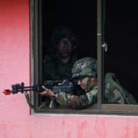 A South Korean soldier aims his weapon during the a joint military exercise with U.S. troops in Pocheon, South Korea, in September 2017.   BLOOMBERG