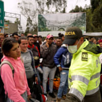 Venezuelans gather to cross into Ecuador from Colombia, most of them trying to reach Peru as one of the most welcoming destinations for migrants in South America, in Tulcan, Ecuador, in June. | REUTERS
