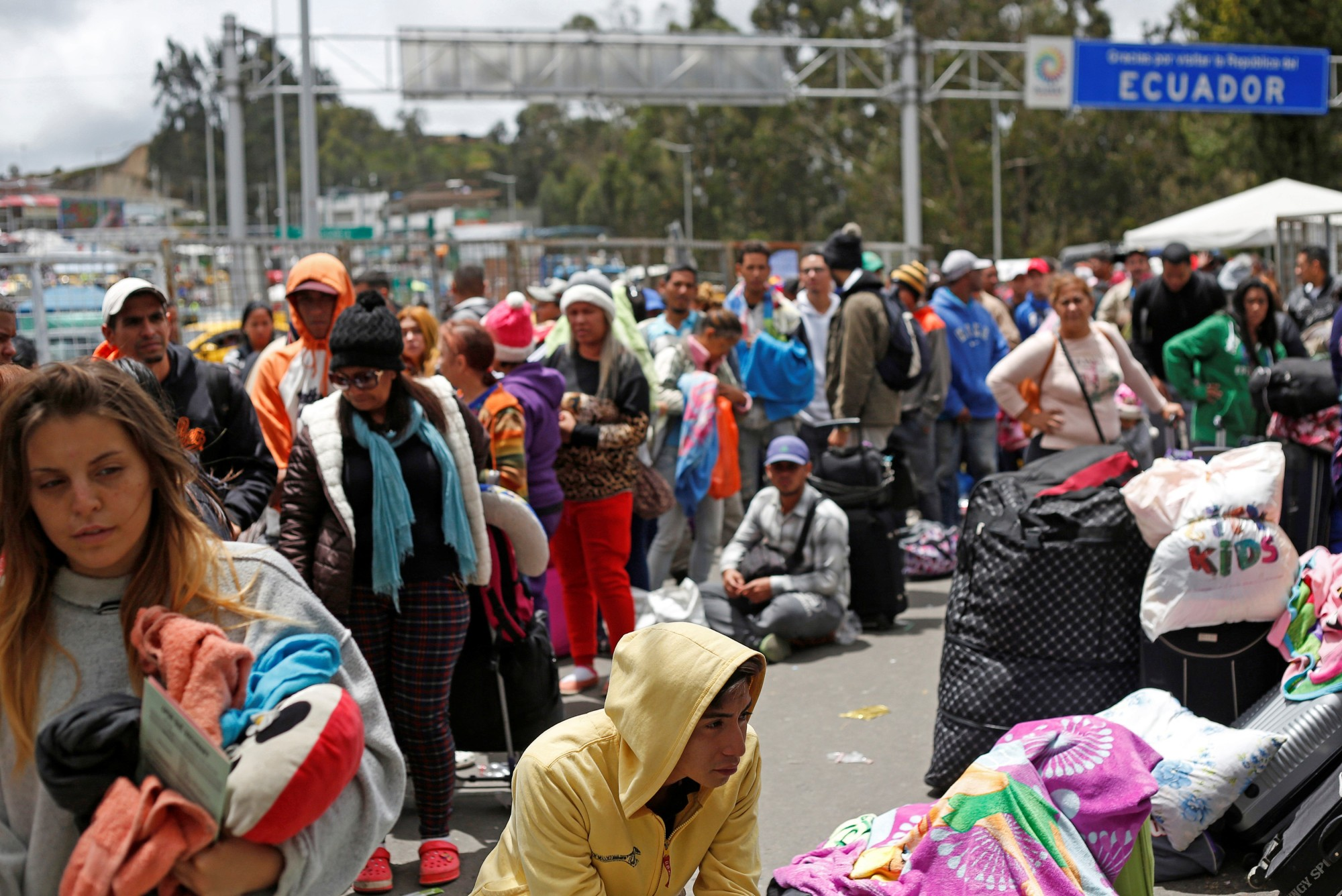 Venezuelan citizens and other migrants wait at the border with Colombia, at the Rumichaca bridge checkpoint, in Ecuador Saturday. Ecuadorean President Lenin Moreno signed a decree requiring Venezuelan citizens, who until now could cross the border with a passport or other form of identification, to have a visa to enter the country. | REUTERS