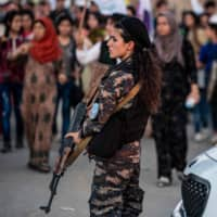 A member of the Kurdish Internal Security Police Force of Asayish stands guard as Syrian Kurds demonstrate against Turkish threats to invade the Kurdish region, in the northeastern city of Qamishli on Tuesday. The Kurdish authorities in northeast Syria said Tuesday their forces had started to withdraw from outposts along the Turkish border after a U.S.-Turkish deal for a buffer zone there. | AFP-JIJI