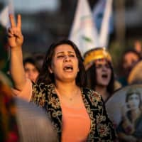 A Syrian Kurdish demonstrator shouts slogans as she marches in the northeastern city of Qamishli on Tuesday during a protest against Turkish threats to invade the Kurdish region. | AFP-JIJI