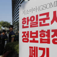 South Korean police officers stand next to a banner during a rally demanding the South Korean government to abolish the General Security of Military Information Agreement (GSOMIA), an intelligence-sharing agreement between South Korea and Japan, in front of Japanese embassy in Seoul, on Thursday. | AP