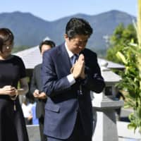 Prime Minister Shinzo Abe and his wife, Akie, visit the grave of his father, Shintaro Abe, in Nagato, Yamaguchi Prefecture, on Tuesday.   KYODO