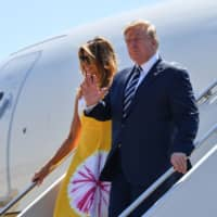 U.S. President Donald Trump waves flanked by his wife, Melania Trump, as they disembark from an airplane upon landing at the Biarritz Pays Basque Airport in Biarritz, southwest France, on Saturday on the first day of the annual G7 Summit.   AFP-JIJI