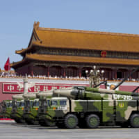Chinese military vehicles carrying DF-21D anti-ship ballistic missiles are paraded past Tiananmen Gate in Beijing in this 2015 file photo. | AP