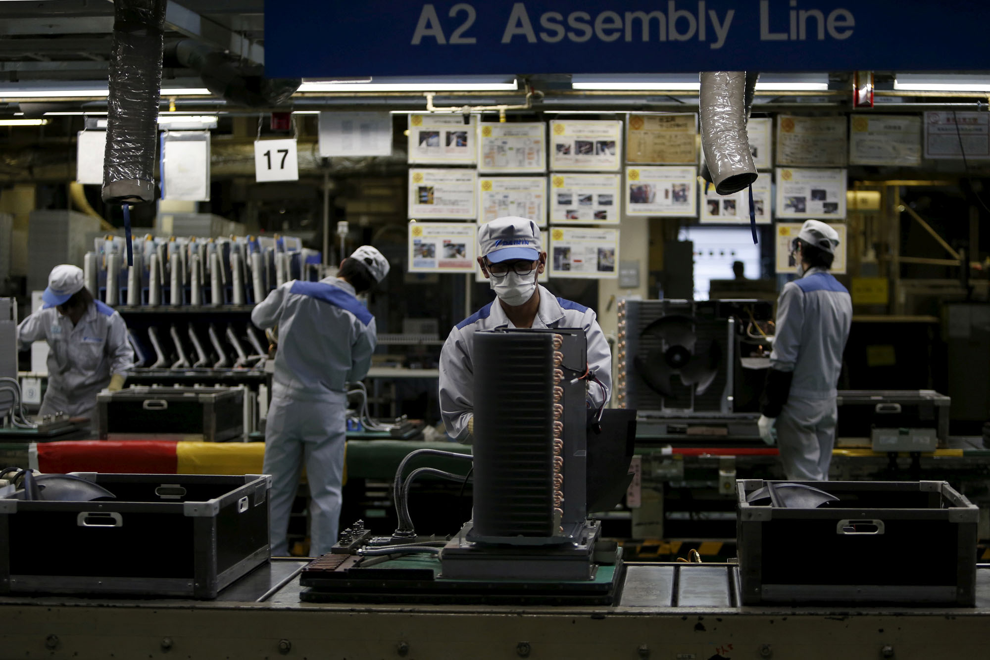 Daikin Industries Ltd. employees produce outdoor air conditioning units at the company's Kusatsu factory in Shiga Prefecture in 2015. | REUTERS